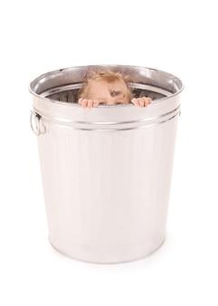 쓰레기통에있는 사랑스러운 아기의 사진 (손에 초점)