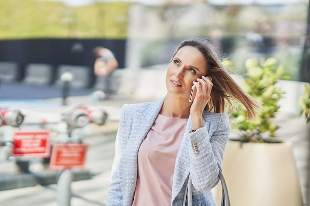 街を歩いているスマートフォンを持つ大人の魅力的な女性の写真