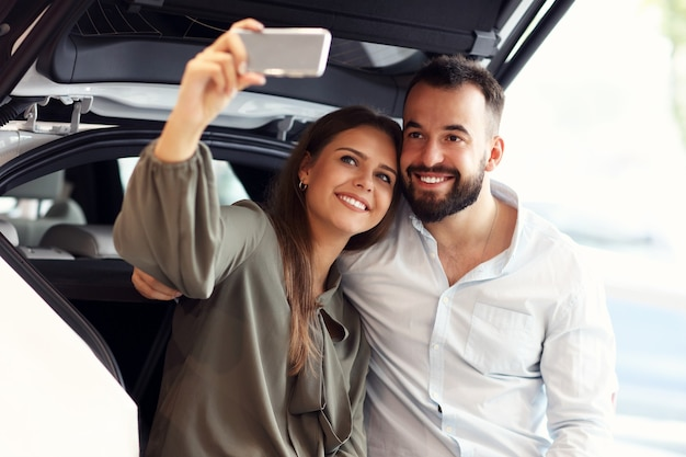 Изображение взрослой пары, выбирающей новый автомобиль в автосалоне
