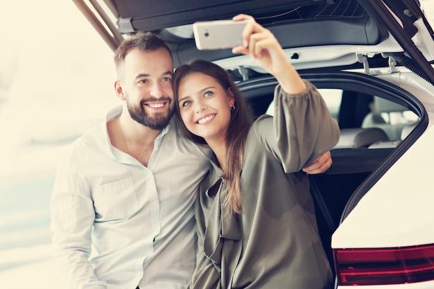 ショールームで新しい車を選ぶ大人のカップルの写真