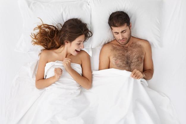 성인 유럽 수염 남자와 흥분된 여자가 침대에 누워 흰 담요 아래 엿보는 사진
