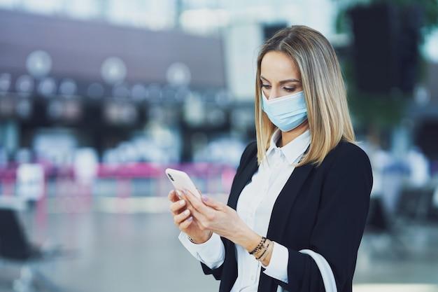 空港でスマートフォンを使用している大人の女性の乗客の写真