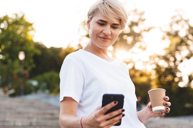 街の階段に立っている間、携帯電話と持ち帰り用のコーヒーを持っているカジュアルな服を着ているブロンドの髪の30代の大人の女性の写真