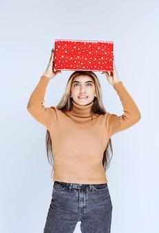 Изображение привлекательной модели женщины, держащей красные накладные расходы настоящего.