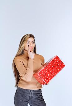 赤いプレゼントを持っている魅力的な女性モデルの写真。