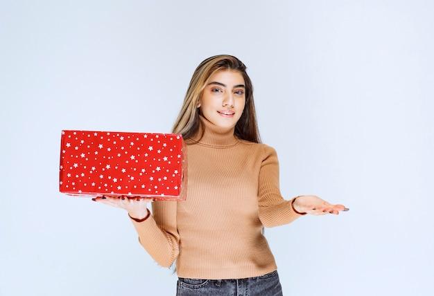 Изображение модели привлекательной женщины, держащей красный подарок.