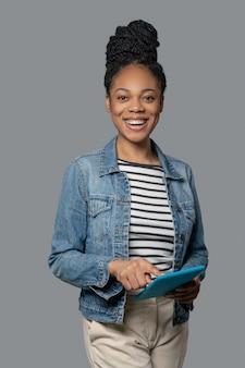 Фотография возбужденной смуглой молодой женщины в джинсовой куртке