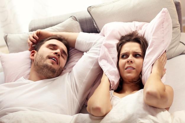 いびきをかく男とベッドで怒っている女性の写真