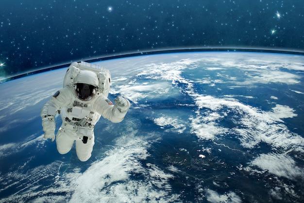 Изображение космонавта в космосе. на заднем плане планета земля. элементы этого изображения предоставлены