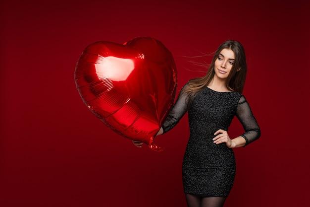 Картина привлекательной кавказской женщины в черном платье с воздушным шаром в руке улыбается на красном