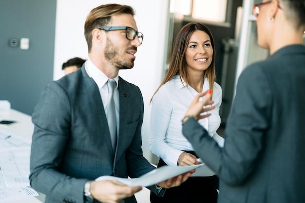 オフィスで話している魅力的なビジネスの同僚の写真