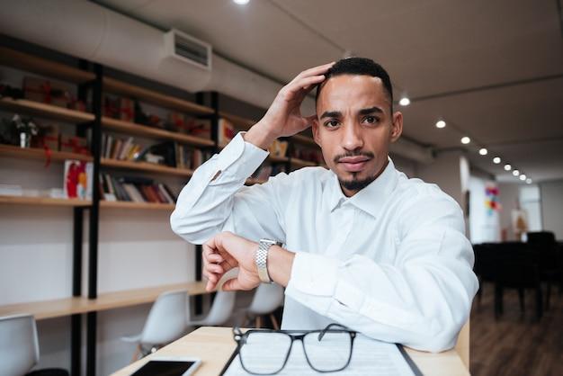 Изображение привлекательного бизнесмена в часах, сидящего за столом, глядя на фронт