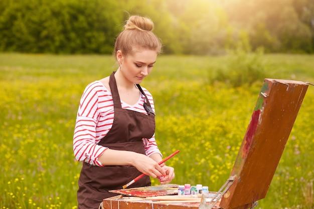色のパレットで魅力的な集中して若い白人女性の立っている写真