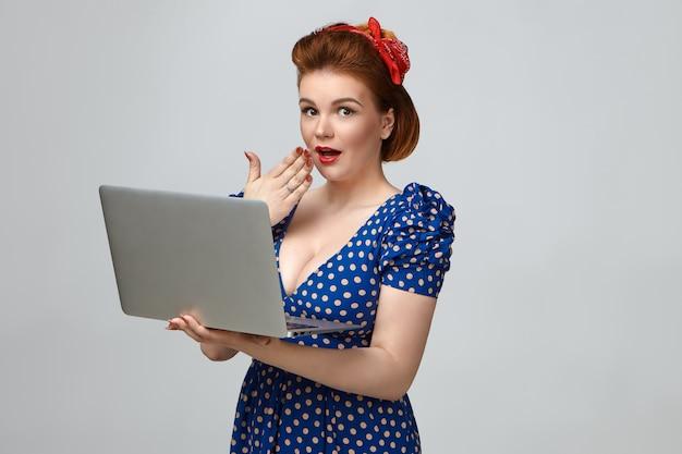 ピンナップスタイルのドレスとレトロな髪型を身に着けている魅力的な魅力的な若い女性の写真は、驚いた表情に衝撃を与え、口を覆い、開いた一般的なラップトップコンピューターを彼女の前に持っています