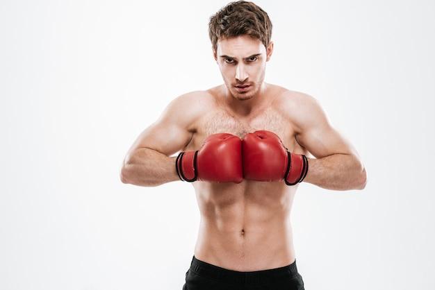 Изображение боксера привлекательного человека, стоящего над белой стеной.