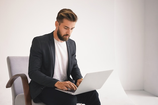 魅力的な成功した若いヨーロッパのひげを生やした男性起業家がリモートで作業し、ポータブルコンピューターで電子メールをチェックし、深刻な表情を持ち、ビジネスの問題に焦点を当てている写真