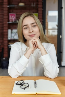 カフェでコーヒーを飲み、マグカップと開いたコピーブックと木製のテーブルに一人で座って、昼食のために友人を待っているブロンドの髪を持つ魅力的な成功した若いヨーロッパの女性作家の写真