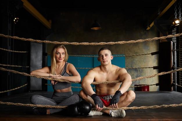 集中的なトレーニングの後、ボクシングのリングの内側の床に足を組んで座っている魅力的な若い運動カップルの男性と女性の写真、幸せな自信を持って、スタイリッシュなスポーツ服を着ています