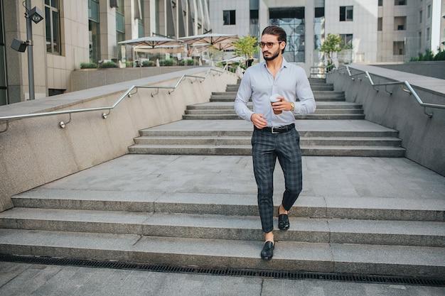 Картина привлекательный молодой человек идет по ступенькам и смотрит налево. он держит чашку кофе в левой руке. парень носит солнцезащитные очки. он выглядит стильно.
