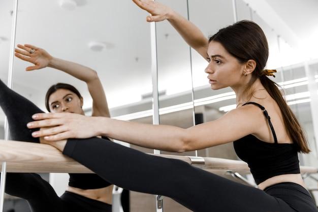 스튜디오에서 발레리나의 그림. 거울 앞에 서서 훈련하는 슬림하고 날씬한 소녀.