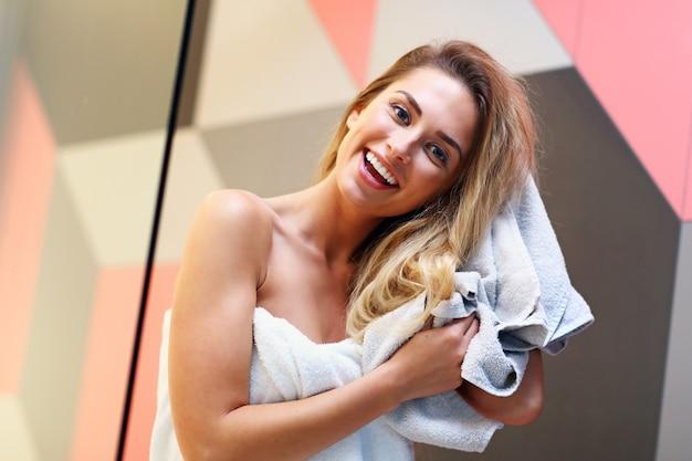 濡れた髪のバスルームでポーズをとる美しい金髪白人女性の写真。