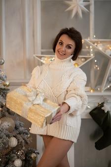 美しい白人女性の写真は、プレゼントと笑顔で大きな箱を持っています
