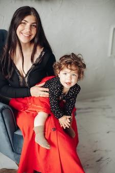 Фотография красивой кавказской девушки с красивым лицом позирует на камеру с ребенком