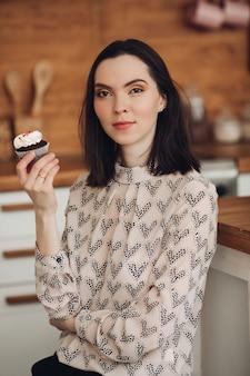 Фотография красивой кавказской девушки с короткими темными волосами в уютном свитере держит зефир и улыбается