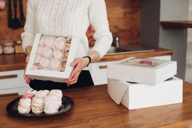 흰색 스웨터에 짧은 검은 머리를 가진 아름다운 백인 여성의 사진에는 큰 흰색 마시멜로가 많은 흰색 상자가 있습니다