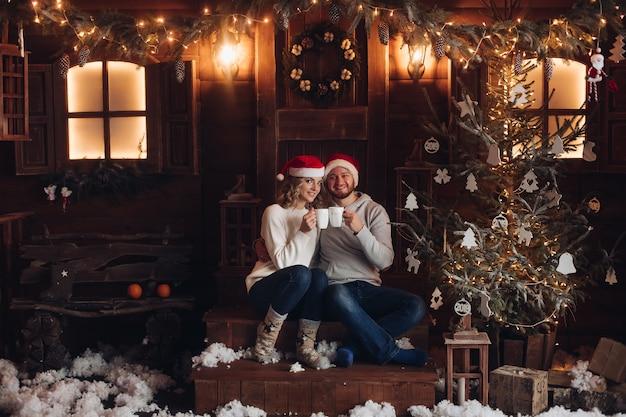彼女のボーイフレンドと一緒に美しい白人女性の写真は家で一緒にクリスマスを祝う