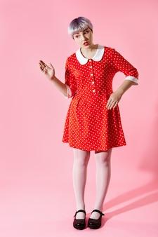 분홍색 벽에 빨간 드레스를 입고 짧은 밝은 보라색 머리를 가진 아름다운 인형 소녀의 그림