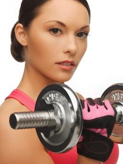 Изображение красивой спортивной женщины с гантелями