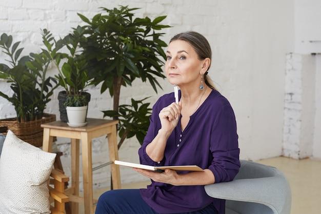 Картина красивой мыслительной зрелой 50-летней писательницы в повседневной одежде, сидящей на удобном стуле в интерьере современной гостиной и делающей записи в тетради, с задумчивым видом
