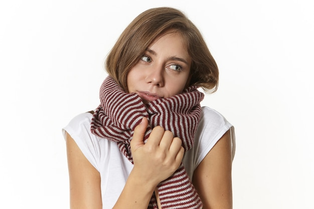 ウールの縞模様のスカーフに包まれてウォーミングアップする白いtシャツの美しい女性の写真