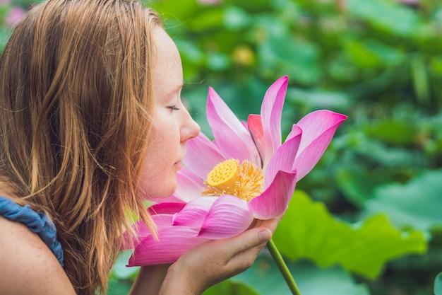 蓮の花を手に赤毛の美女の写真。