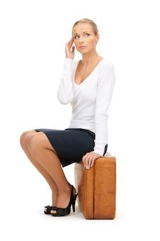 茶色のスーツケースを持つ美しい女性の写真