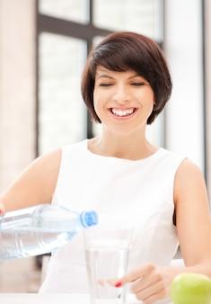 水のガラスを持つ美しい女性の写真