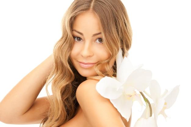 蘭の花を持つ美しい女性の写真