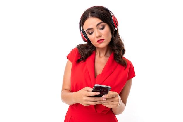 Фотография красивой молодой кавказской девушки с длинными темными волосами и ярким макияжем в красном платье делает селфи со своим телефоном, изолированным на белом фоне