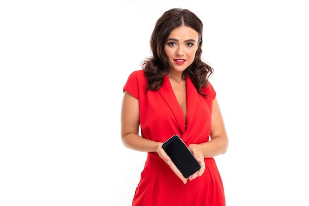 Фотография красивой молодой кавказской девушки с длинными темными волосами и ярким макияжем в красном платье с телефоном на белом фоне