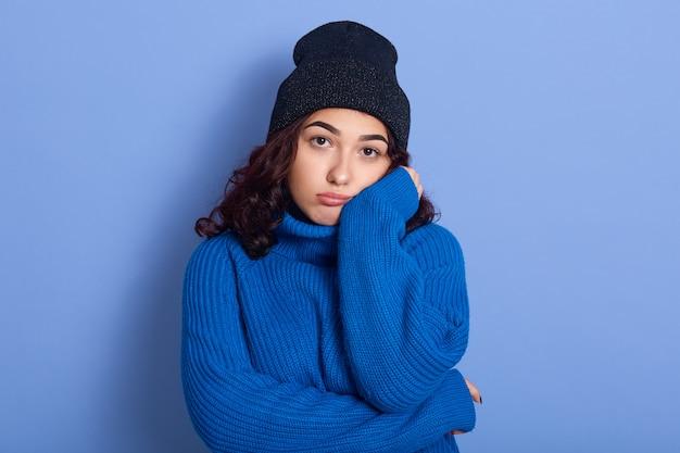 파란색 모자와 스웨터를 입고 손으로 그녀의 얼굴을 만지고 지루한 불만족 어두운 머리 젊은 여성 서 스튜디오에서 파란색 이상 격리의 그림. 사람과 권태 개념.