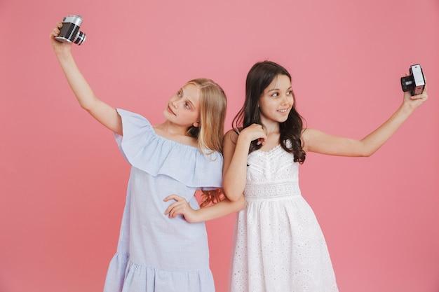 Фотография очаровательных брюнеток и блондинок в платьях, улыбающихся и делающих селфи на ретро-камеры, изолированные на розовом фоне