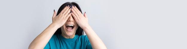 手で顔を覆い、指から覗くブルネットの10代の少女の写真。