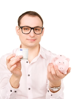 貯金箱とお金を持つビジネスマンの写真