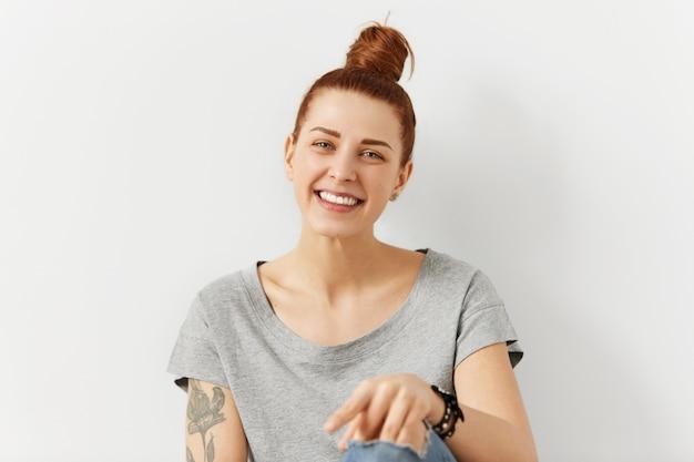 魅力的でカリスマ的な若い白人女性の写真は、カジュアルでトレンディでスタイリッシュな格好で、肩に入れ墨があり、のんきな表情で笑っています。人とライフスタイルのコンセプト