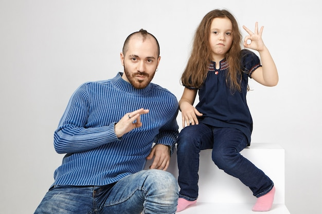 魅力的な女性の子供がスタジオに座って、カメラで大丈夫なジェスチャーを示しているひげを生やしたお父さんと自由な時間を楽しんでいる写真、つまりすべてが順調です