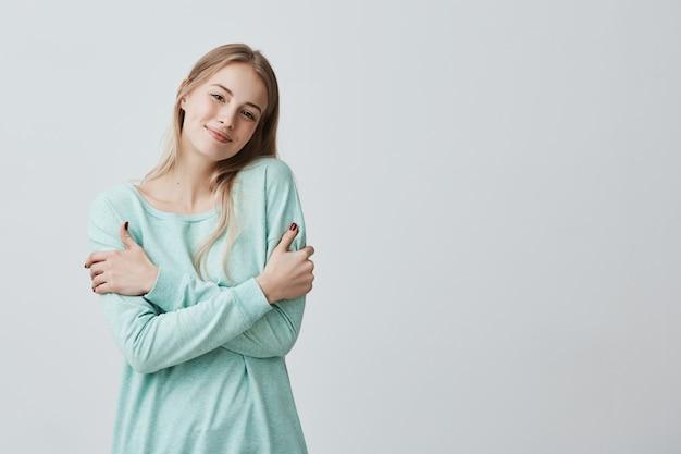 青いセーターに身を包んだ陽気な美しい若いヨーロッパの女性が幸せそうに笑って、彼女を抱きしめ、彼女の顔に肯定的な楽しい表情を持っている写真。人、ライフスタイル、そして幸せ