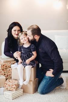 예쁜 여자 아기와 함께 쾌활한 백인 가족의 사진은 새해나 크리스마스를 축하합니다...