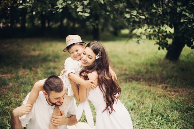 쾌활한 백인 엄마, 아빠, 그리고 그들의 아이가 정원에서 함께 즐거운 시간을 보내고 미소를 짓는 사진