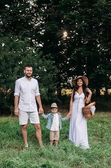 陽気な白人のお母さん、お父さんとその子供が一緒に楽しんで、庭で笑顔の写真